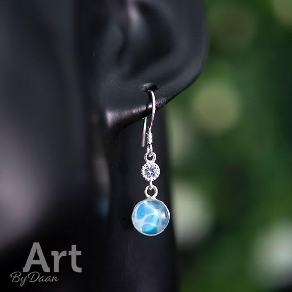 Subtiele zilveren oorbellen met blauwe steen