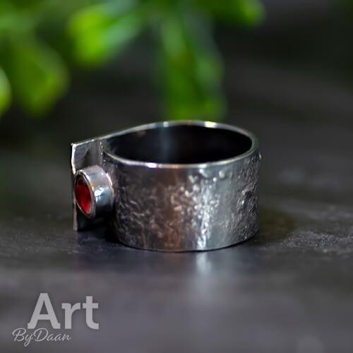 Brede zwarte handgesmede ring met rode steen