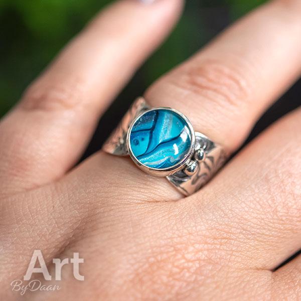 Brede handgesmede zilveren ring met helderblauwe steen