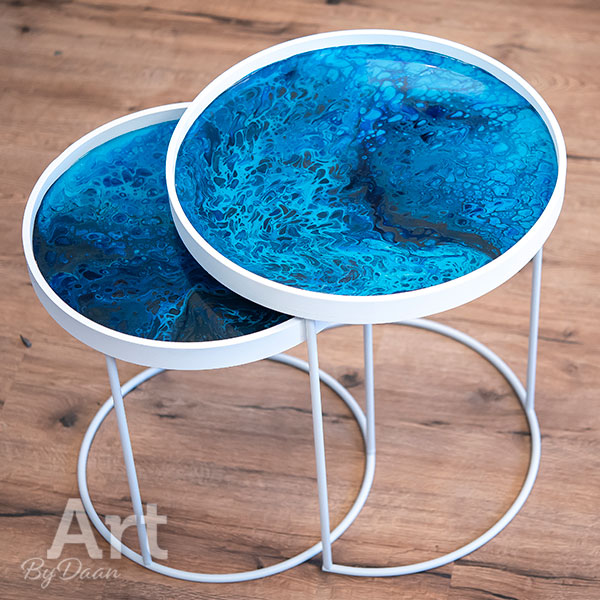 Unieke set witte bijzettafels met blauw kunstwerk