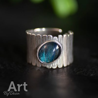 Aparte brede ring met ovale blauwe steen